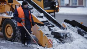 Tractor cleaning the road from the snow. Excavator cleans the streets of large amounts of snow in city. Workers sweep. Removing snow with plow. Close up of iron stock video