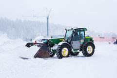 Tractor cleaning snow in field stock image