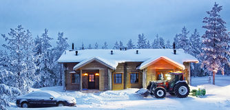 Tractor cleaning snow near cottage in forest Royalty Free Stock Photos