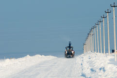 Tractor cleaning snow on the road after a snowfall Stock Photo