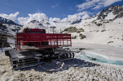Tractor cleaning snow on the ski slopesto the top of the mountain at an altitude of 2400 meters in the Alps Royalty Free Stock Photo
