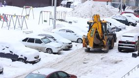 Tractor cleaning snow in winter snowy day in city. Winter service vehicle in work. Snow removal vehicle stock footage