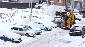 Tractor cleaning snow in winter snowy day in city. Winter service vehicle in work. Snow removal vehicle stock video footage