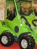 Tractor for cleaning streets. Green tractor on black rubber wheels for cleaning sidewalks and streets royalty free stock image