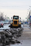 tractor cleans the road in the city of dirty snow Royalty Free Stock Image