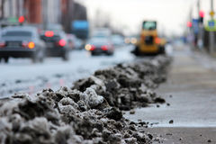 tractor cleans the road in the city of dirty snow Royalty Free Stock Images