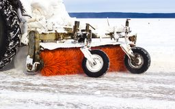 Tractor cleans road from snow after blizzard. Bad winter weather conditions and transport service concept. Stock Image