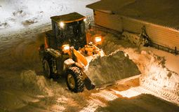 Tractor cleans the snow. Night cleaning of snow with  bulldozer after  snowfall. The grader rakes the snow in  big pile at night. The tractor cleans  snow. Night Royalty Free Stock Photos