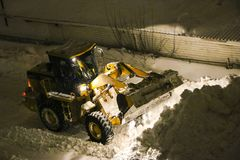 Tractor cleans the snow. Night cleaning of snow with bulldozer after snowfall. The grader rakes the snow in big pile at night stock photos