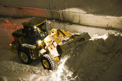 Tractor cleans the snow. Night cleaning of snow with  bulldozer after  snowfall. The grader rakes the snow in  big pile at night. The tractor cleans  snow. Night Royalty Free Stock Photography