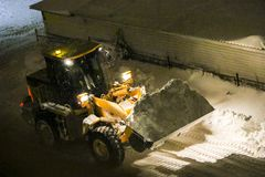 Tractor cleans the snow. Night cleaning of snow with  bulldozer after  snowfall. The grader rakes the snow in  big pile at night. The tractor cleans  snow. Night Stock Image