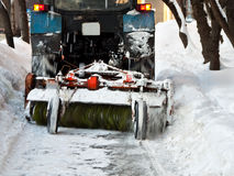 Tractor clears snow. A tractor cleaning the sidewalk during a snow storm Stock Images