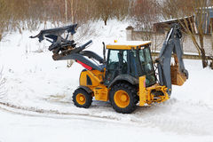 Tractor clears snow outside winter Stock Photography