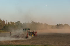Tractor in a cloud of dust plows autumn field Royalty Free Stock Photos