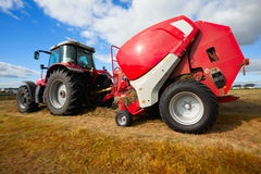 Tractor collecting haystack in the field Royalty Free Stock Photos