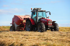 Tractor collecting haystack in the field Stock Image