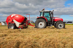 Tractor collecting haystack in the field Stock Photos