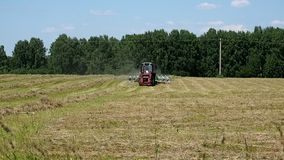 Tractor collecting mown hay stock video