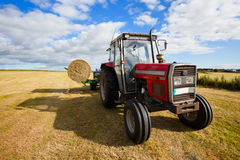 Tractor collecting a roll of haystack in the field Royalty Free Stock Image