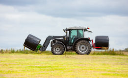 Tractor collecting a roll of haystack in the field Stock Photos