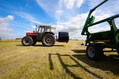 Tractor collecting a roll of haystack in the field Royalty Free Stock Photography