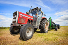 Tractor collecting a roll of haystack in the field Royalty Free Stock Photos