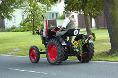 Tractor colored. Colored tractor decorated for harvest party with an elderly man royalty free stock image