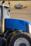 Tractor and combine harvesting wheat in rural field Stock Photo