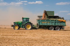 Tractor and combine John Deere on harvested field Royalty Free Stock Photo