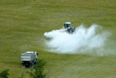 A tractor commencing spraying field with lime/insecticide/pesticide. A farm tractor setting off up a hilly field to begin spraying grass/crop with insecticide/ stock images