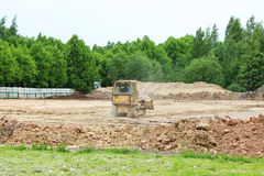 Tractor and compactor are leveling and compacting the surface of the earth. Construction of the city stadium. Tractor and compactor are leveling and compacting Royalty Free Stock Images