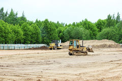 Tractor and compactor are leveling and compacting the surface of the earth. Construction of the city stadium. Tractor and compactor are leveling and compacting Stock Photos