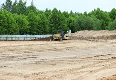 Tractor and compactor are leveling and compacting the surface of the earth. Construction of the city stadium. Tractor and compactor are leveling and compacting Royalty Free Stock Image