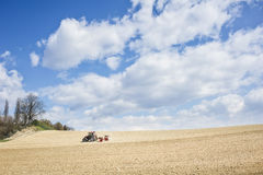 Tractor compresses the soil after planting with rollers. Royalty Free Stock Photos