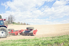 Tractor compresses the soil after planting with rollers. Stock Image