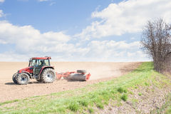 Tractor compresses the soil after planting with rollers. Royalty Free Stock Photo