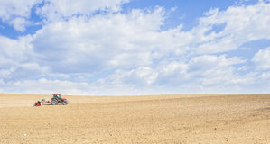 Tractor compresses the soil after planting with rollers. Royalty Free Stock Images