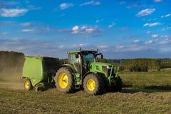 Tractor con la maquinaria para hacer las balas del heno Foto de archivo libre de regalías