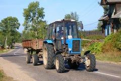 Tractor con un remolque en el pueblo ruso foto de archivo