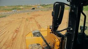 Tractor con un suelo móvil de la niveladora en un emplazamiento de la obra metrajes