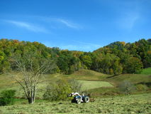 Tractor in countryside. Scenic view of countryside fields and wooded hillside with tractor in foreground Stock Photo