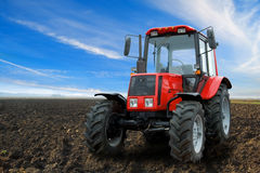 Tractor in countryside. Closeup of modern red tractor on countryside field under blue sky and cloudscape Royalty Free Stock Photography