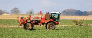 Crop sprayer spraying in crop field. Tractor crop spraying in bateman 5000 in english crop field Royalty Free Stock Image