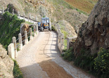 Tractor crossing La Coupee on Sark Royalty Free Stock Photography