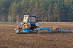 Tractor cultivates box spring. The spring agricultural fieldwork mechanized equipment Stock Photography