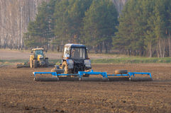 Tractor cultivates box spring. The spring agricultural fieldwork mechanized equipment Stock Images