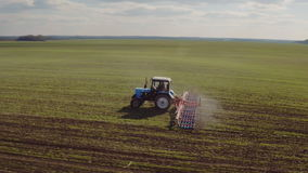 The tractor cultivates the land in the field in early spring. The camera flies around. 4K video stock video footage