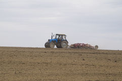 The tractor cultivates the soil in the spring. In the photo the tractor treats the soil in the spring Stock Photos