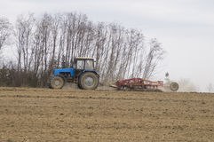 The tractor cultivates the soil in the spring. In the photo the tractor treats the soil in the spring Stock Photography
