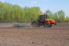 Tractor cultivating the field Stock Photos